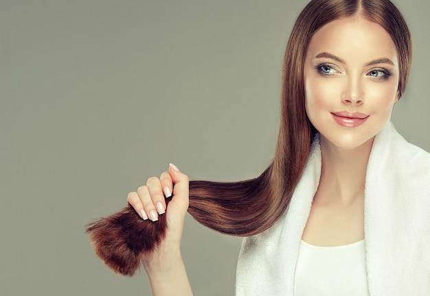 Bela jovem modelo de cabelos castanhos com cabelo comprido e reto está segurando o rabo de um cabelo bem tratado e saudável na mão. beleza natural e saúde do cuidado do cabelo.