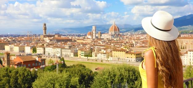 Bela jovem modelo feminino com chapéu na cidade de florença com a catedral e o palazzo vecchio no fundo, florença, toscana, itália.