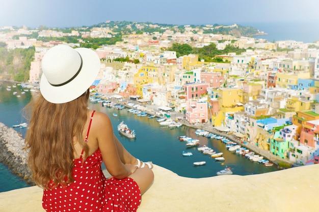 Bela jovem modelo feminino com chapéu na ilha de procida, com o porto de marina di corricella e a vila ao fundo, procida, itália.
