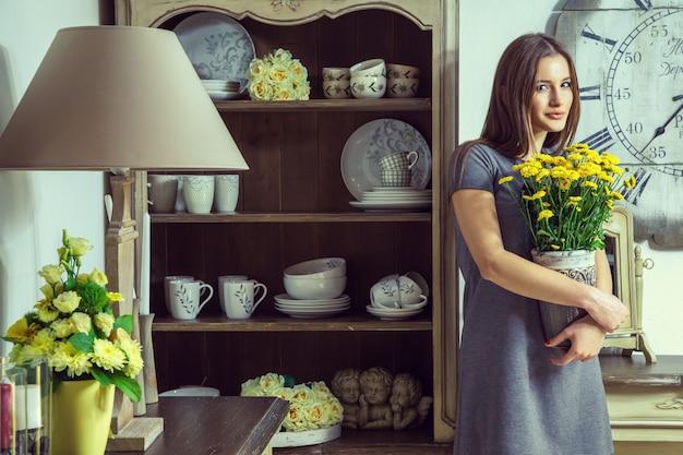 Bela jovem modelo segurando flores amarelas