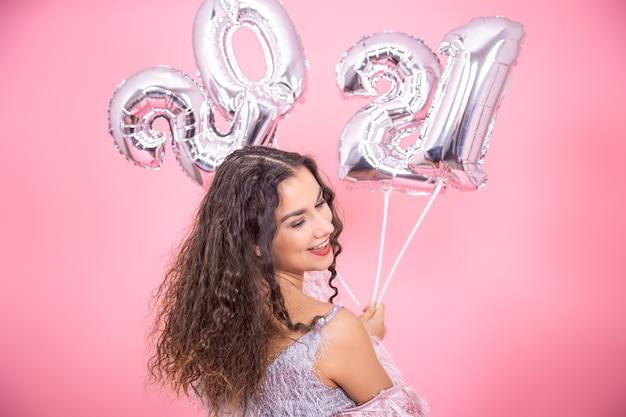 Bela jovem morena com cabelos cacheados e ombros nus sorrindo em um fundo rosa com balões prateados para o conceito de ano novo