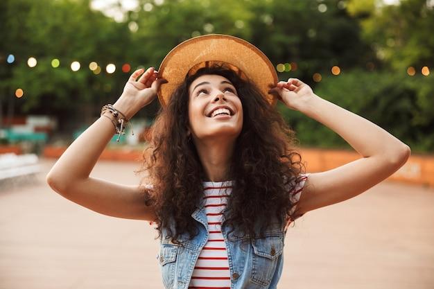 Bela jovem morena de chapéu de palha, aproveitando o verão e caminhando no parque verde