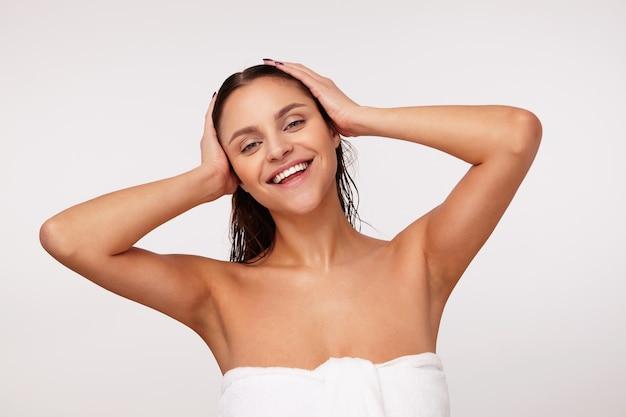 Bela jovem morena de olhos verdes com aparência agradável, segurando as palmas das mãos sobre a cabeça molhada e sorrindo sinceramente, posando após o banho