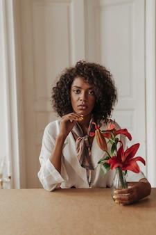 Bela jovem morena encaracolada com blusa branca elegante se inclina sobre a mesa de madeira, olha para a frente e toca o vaso com flores vermelhas