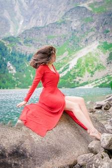 Bela jovem morena esguia em um vestido vermelho perto do lago morskie oko ou sea eye, parque nacional tatra, polônia