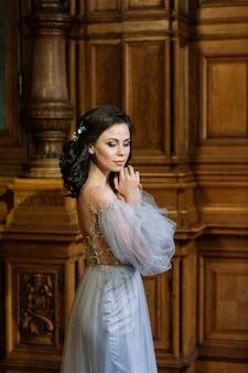 Bela jovem morena noiva em um elegante vestido de noiva e penteado em hotel no interior de luxo.
