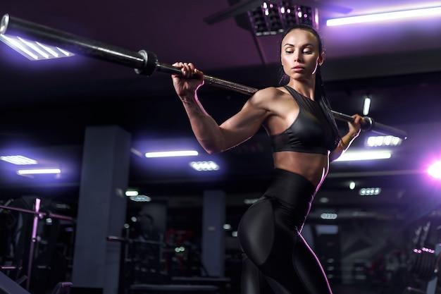 Bela jovem morena sexy, atleta fisiculturista, exercícios na academia, em lindas roupas esportivas