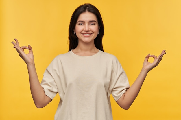 Bela jovem morena sorridente em uma camiseta branca sobre amarela mantém as mãos no gesto mudra zen meditando e fazendo ioga na parede