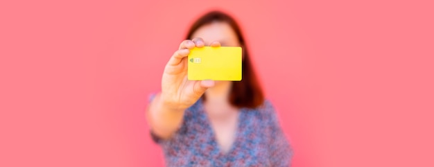 Bela jovem mostrando um cartão de plástico em branco perto de uma parede rosa na rua