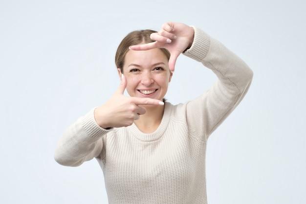 Bela jovem mostrando uma moldura com as mãos e sorrindo amigavelmente