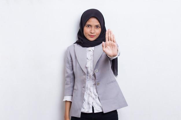Bela jovem muçulmana com a mão aberta fazendo um sinal de pare com um gesto sério de defesa de expressão