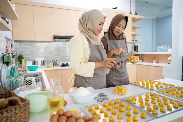 Bela jovem muçulmana segurando o tablet pc enquanto assa um bolo de nastar em casa