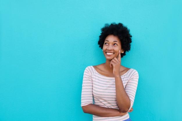 Bela jovem mulher africana sorrindo e pensando