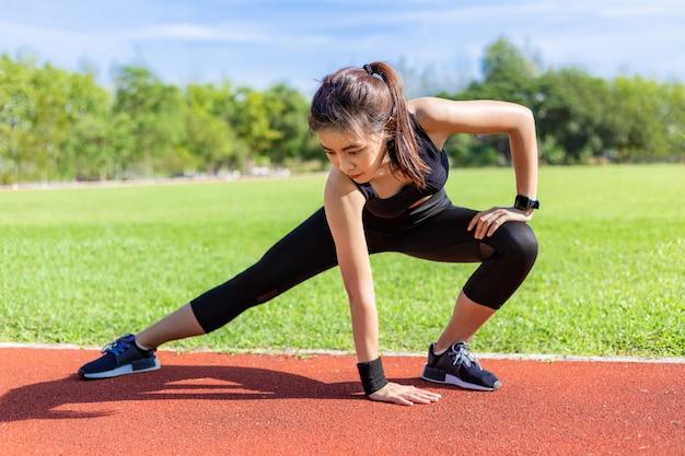 Bela jovem mulher asiática alongamento antes do exercício da manhã em uma pista de corrida