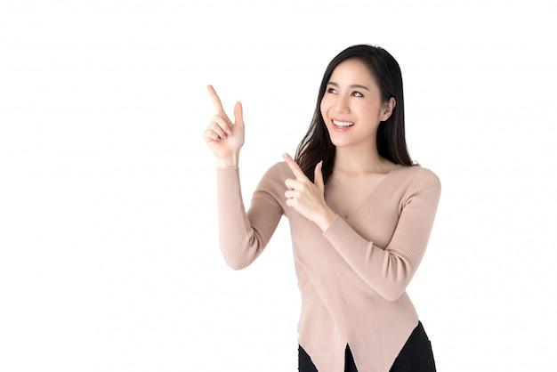 Bela jovem mulher asiática, apontando as mãos para esvaziar o espaço de lado