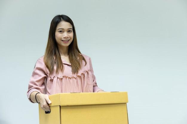 Bela jovem mulher asiática com caixa de papelão na mão