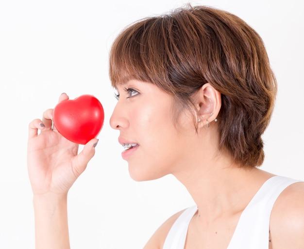 Bela jovem mulher asiática com coração vermelho. conceito de saúde cardiovascular.