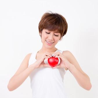 Bela jovem mulher asiática com coração vermelho, isolado no branco
