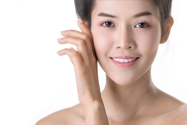 Bela jovem mulher asiática com cosméticos no próprio rosto