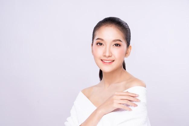 Bela jovem mulher asiática com rosto de pele branca fresca limpa em pose de beleza tocando o ombro com o dedo