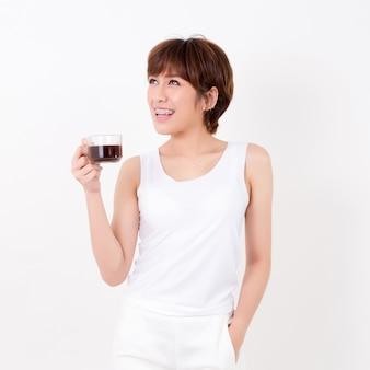 Bela jovem mulher asiática com uma xícara de café quente.