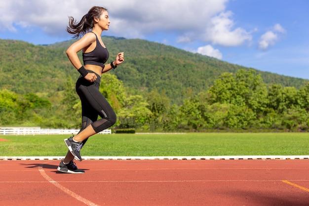 Bela jovem mulher asiática correndo exercício de manhã em uma pista de corrida