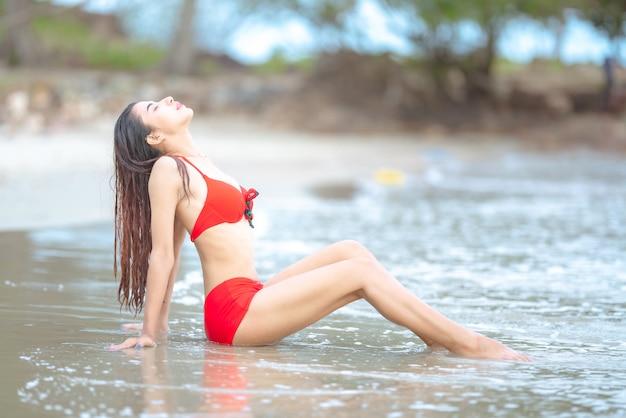 Bela jovem mulher asiática em biquíni relaxante na praia de areia, viajar ao ar livre conceito de férias de verão