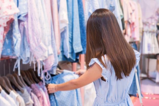 Bela jovem mulher asiática em vestido azul, panos de moda em lojas de departamento,