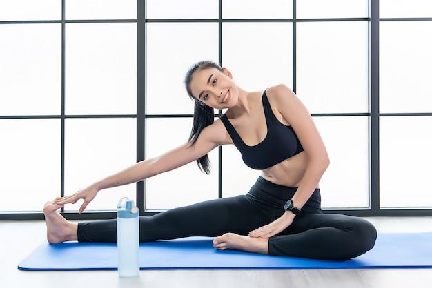 Bela jovem mulher asiática na aula de yoga