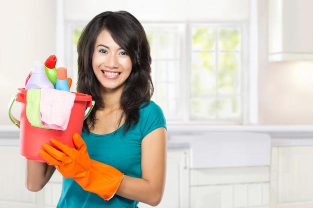 Bela jovem mulher asiática segurando uma cesta cheia de produtos de limpeza