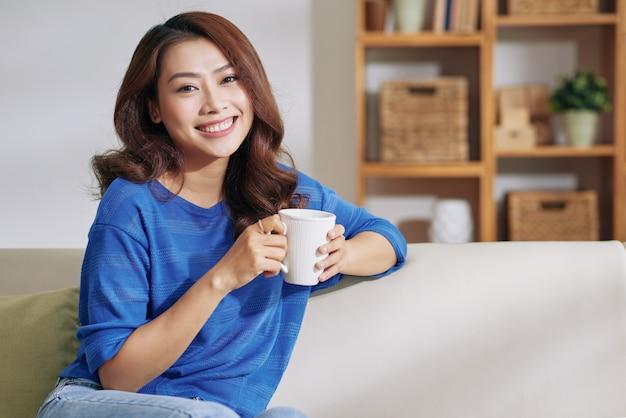 Bela jovem mulher asiática, sentada no sofá em casa com caneca e sorrindo