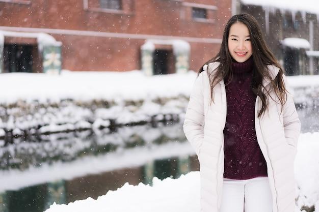 Bela jovem mulher asiática sorrir e feliz com viagem de viagem no canal otaru hokkaido japão
