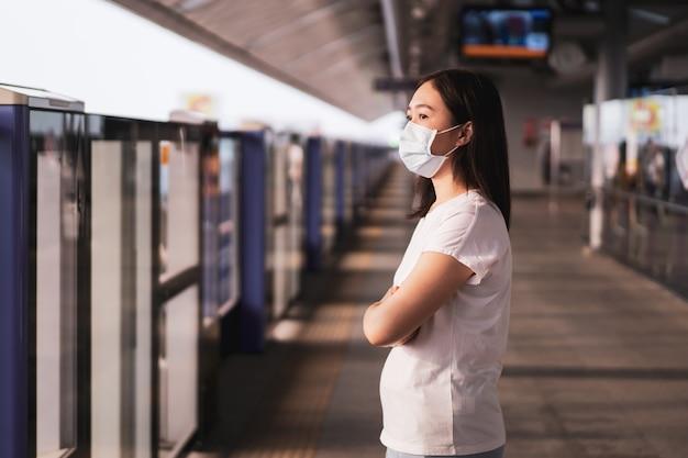 Bela jovem mulher asiática usando a máscara protetora enquanto viaja na cidade