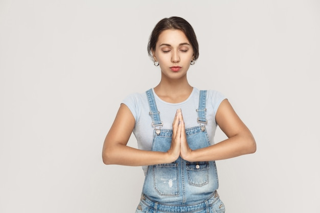 Bela jovem mulher branca, de mãos dadas em namastê ou oração, mantendo os olhos fechados enquanto pratica ioga e medita em casa sozinha. estúdio em fundo cinza.