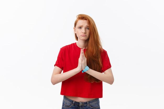Bela jovem mulher branca, de mãos dadas no namastê ou oração, mantendo os olhos fechados enquanto pratica ioga.