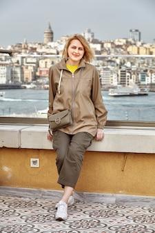 Bela jovem mulher branca posando para o fotógrafo no contexto da paisagem urbana de istambul, com vista para o distrito de beyoglu e a torre galata.