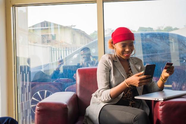Bela jovem mulher de negócios africana se sentindo animada com o que viu em seu telefone inteligente
