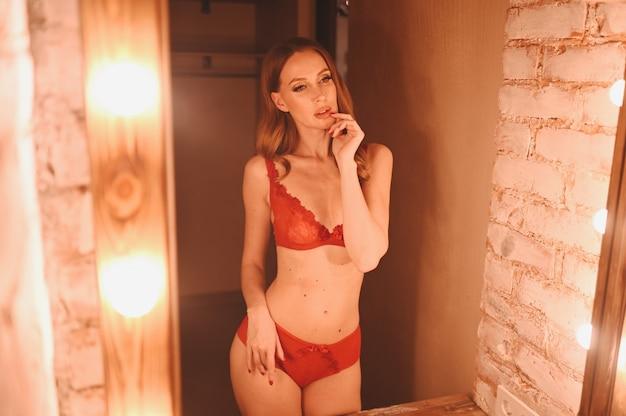Bela jovem mulher sexy de beleza natural olha para o reflexo e posa no espelho de maquiagem estilo hollywood em roupa íntima de renda vermelha