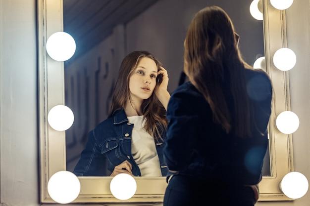 Bela jovem mulher sexy olhando no espelho, tocando seu cabelo, sentado na cadeira no camarim com quarto escuro espelho vintage. foto de estúdio