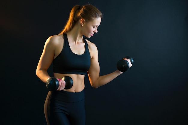 Bela jovem mulher treinando com halteres em um fundo preto