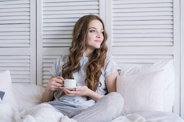 Bela jovem na cama no quarto tomando café da manhã