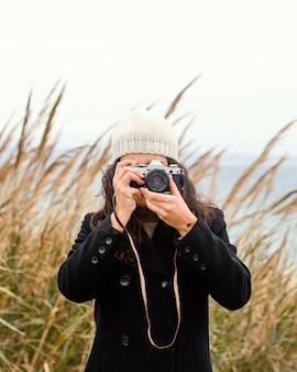 Bela jovem na natureza com câmera