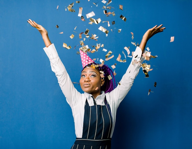 Bela jovem negra comemorando aniversário ou festa de ano novo e chrismas enquanto soprando decorações de confetes para câmera isolada sobre o espaço azul