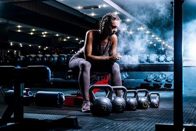 Bela jovem negra desportista no ginásio realiza um treino