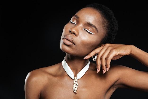 Bela jovem negra posando com os olhos fechados, isolados na parede preta