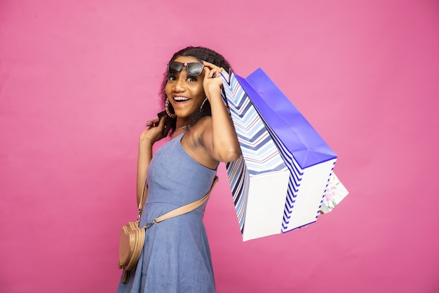 Bela jovem negra segurando sacolas de compras e se sentindo animada