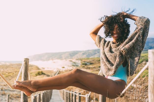 Bela jovem negra sentada em uma ponte de madeira na praia