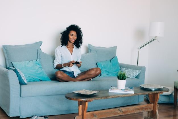 Bela jovem negra sentada no sofá jogando videogame