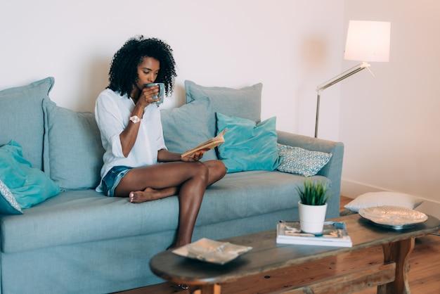 Bela jovem negra sentada no sofá lendo um livro e tomando café