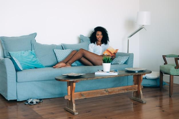 Bela jovem negra sentada no sofá lendo um livro